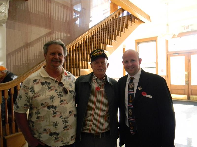 Three men stand together in hallway, one in patriotic t-shirt, one in World War II veteran's hat, and one in black suit, all three smile for camera